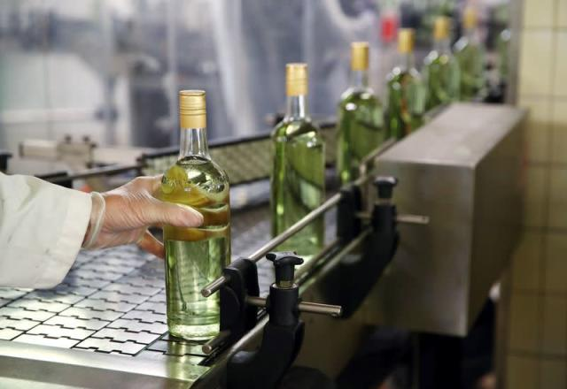 Staff lines a bottle into a labeller at Swiss distiller Morand in Martigny