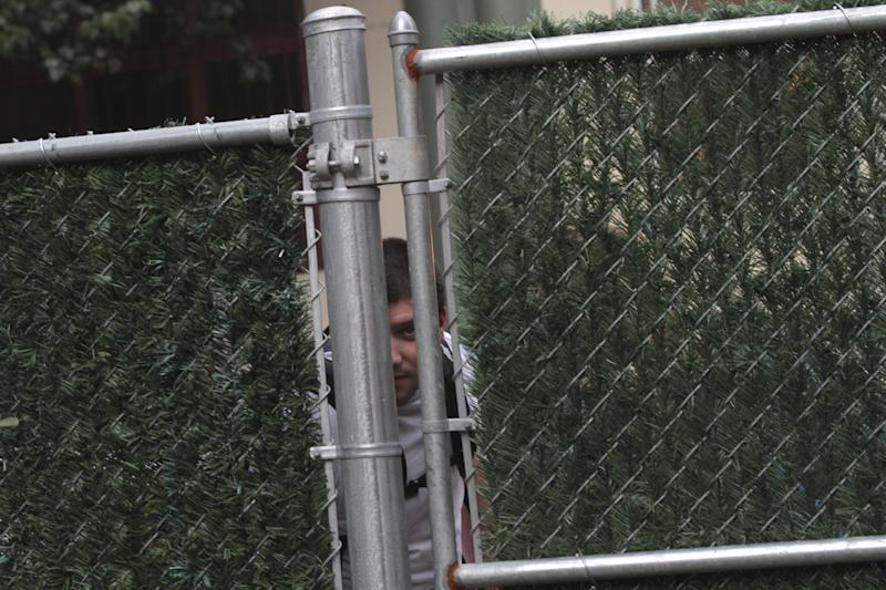 In this Wednesday, July 25 2012 photo, a man peaks through the fence at the activities inside Timeshare Backyard on the Lower East Side of Manhattan. The city's lone timeshare backyard allows New Yorkers to invite up to 30 guests for two hours at a time and comes with grills, lounge chairs and trashy magazines. (AP Photo/Mary Altaffer)