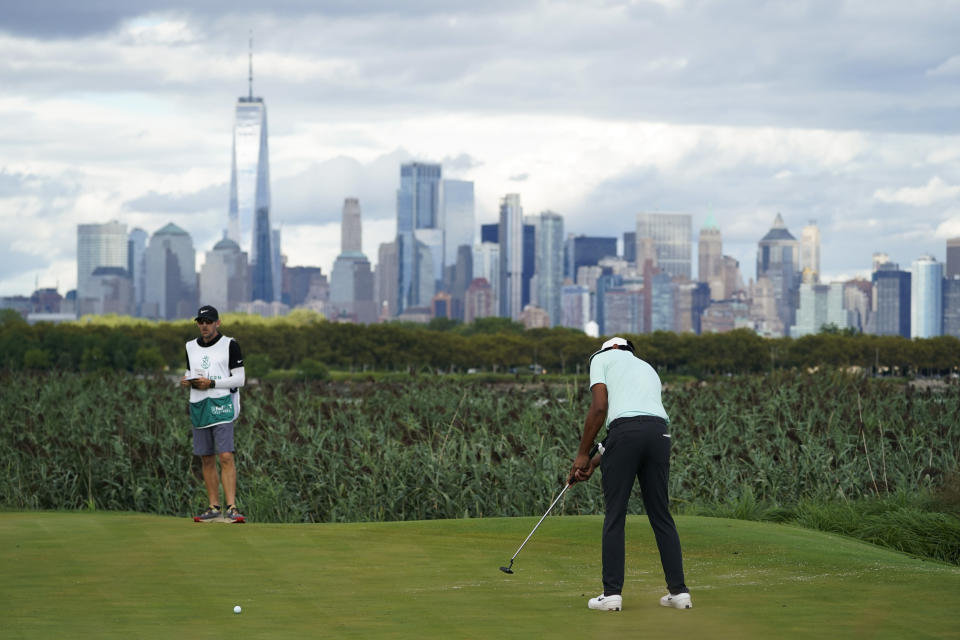 Tony Finau makes a putt on the 14th hole in the final round at The Northern Trust golf tournament at Liberty National Golf Course Monday, Aug. 23, 2021, in Jersey City, N.J. (AP Photo/John Minchillo)