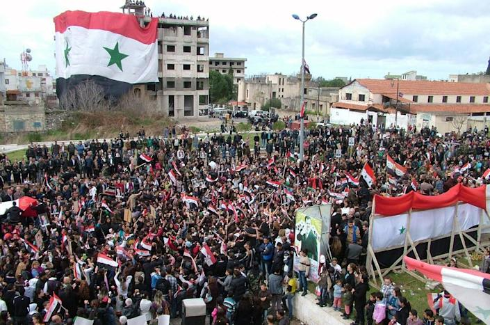 Demonstrators hold portraits of Syrian President Bashar al-Assad and wave national flags in the town of al-Qardaha (AFP Photo/)