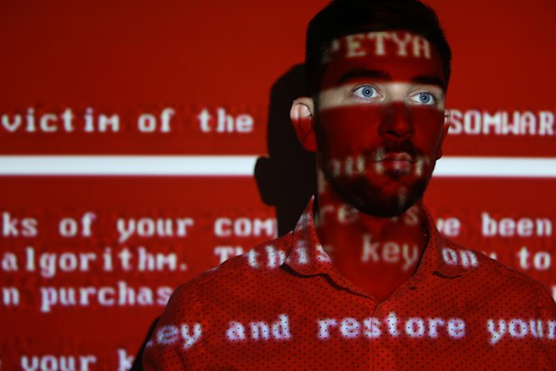 RYAZAN, RUSSIA - JUNE 28, 2017: A message related to the Petya ransomware projected on a young man; on 27 June 2017 a variant of the Petya ransomware virus hit computers of companies in Russia, Ukraine, and other countries in a cyber attack. Alexander Ryumin/TASS (Photo by Alexander Ryumin\TASS via Getty Images)
