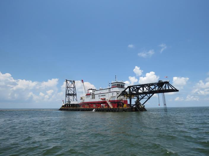 The cutter head dredge R.S. Weeks pumps sand and water from the Gulf of Mexico to a Louisiana barrier island five miles away on Wednesday, July 28, 2021. The flexible pipe on the surface to its left connects to rigid pipe on the bottom. Contractors are at work on a $102 million Louisiana Coastal Restoration and Protection Authority project to add about 400 acres of beach, dune and marshland to Grand Terre Island. Weather permitting, they hope to finish in November. (AP Photo/Janet McConnaughey)