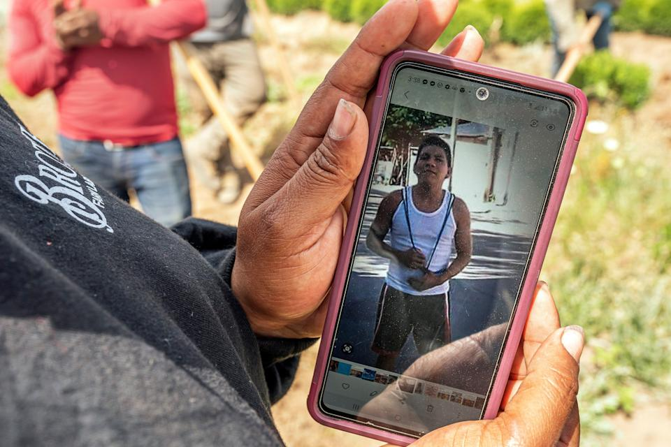 A worker, who declined to be named, looks at a photo of Sebastian Francisco Perez who died last weekend while working in an extreme heat wave, Thursday, July 1, 2021, near St. Paul, Ore. (AP Photo/Nathan Howard) ORG XMIT: ORNH202