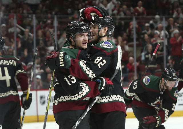 Arizona Coyotes' Vinnie Hinostroza (13) celebrates with teammate Jordan Oesterle (82) after scoring a second-period goal against the Tampa Bay Lightning during an NHL hockey game, Saturday, Oct. 27, 2018, in Glendale, Ariz. (AP Photo/Ralph Freso)