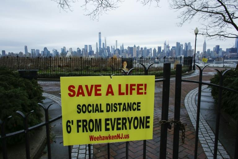 A sign encouraging social distancing to stop the spread of coronavirus is displayed in a park in New Jersey, with the New York city skyline in the background (AFP Photo/Kena Betancur)