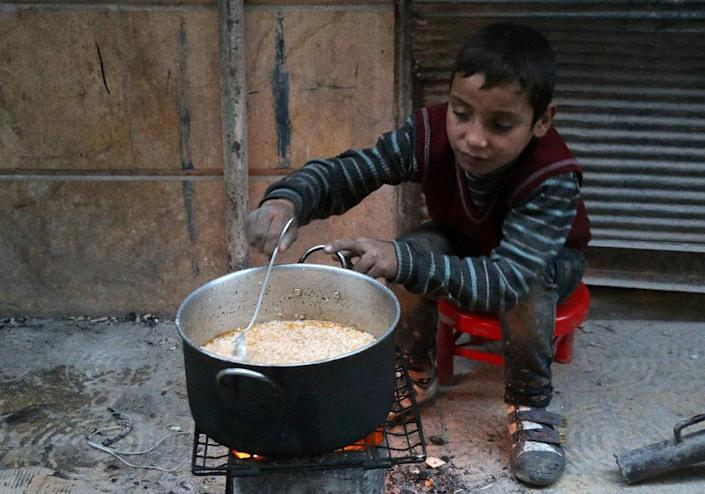 A child cooks on November 13, 2016, in the streets of a rebel-held area of the city of Aleppo, where at least 62 children have been killed since mid-November (AFP Photo/)