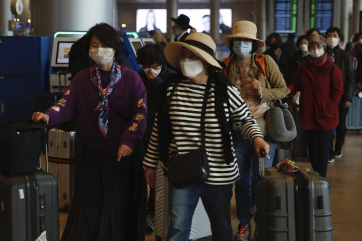 "<span class=""caption"">Tourists wearing protective masks from Korea walk through Ben Gurion Airport near Tel Aviv, Israel.</span> <span class=""attribution""><a class=""link rapid-noclick-resp"" href=""http://www.apimages.com/metadata/Index/Israel-Coronavirus-Outbreak/10dd39c16da343cd9277b75fbd6b8408/1/0"" rel=""nofollow noopener"" target=""_blank"" data-ylk=""slk:AP Photo / Ariel Schalit"">AP Photo / Ariel Schalit</a></span>"