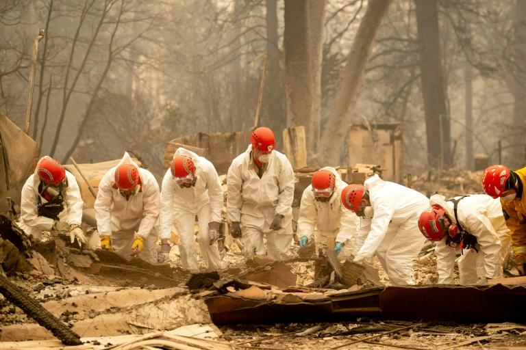 Rescue workers sift through rubble in search of human remains at a burned property in Paradise, California