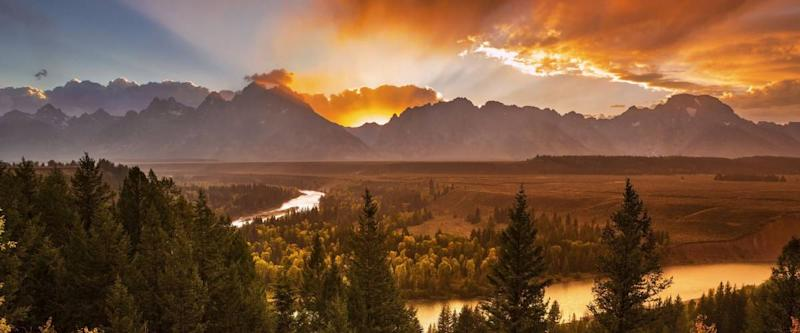 The sun sets behind the Teton Range and Snake River in Grand Teton National Park, Wyoming.