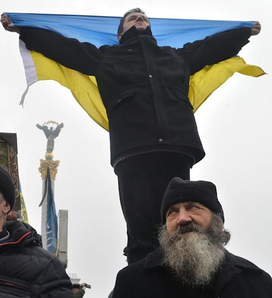 An Orthodox priest stands by an activist holding an Ukrainian flag during a mass rally of the opposition, on Independence Square in Kiev, on February 9, 2014
