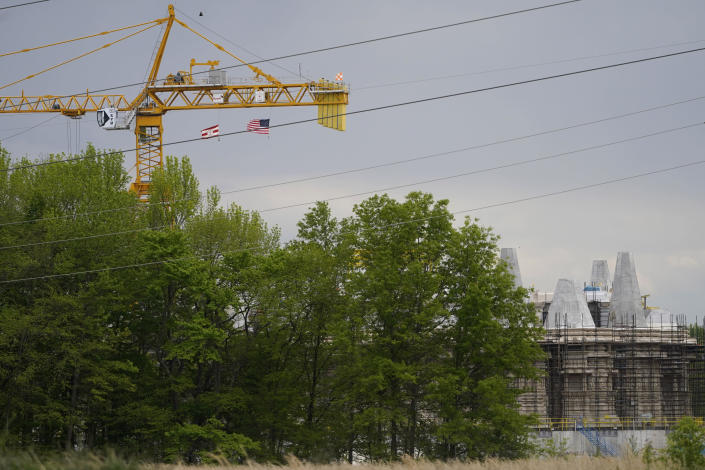 A large crane stands over the under construction BAPS Shri Swaminarayan Mandir in Robbinsville Township, N.J., Tuesday, May 11, 2021. A lawsuit claims workers from marginalized communities in India were lured to New Jersey and forced to work more than 12 hours per day at slave wages to help build a Hindu temple. (AP Photo/Seth Wenig)