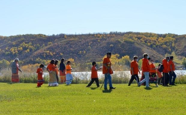 Members of Star Blanket Cree Nation take part in a smudge walk around the grounds of the former Lebret Indian Industrial School in Lebret, Sask., on Sept. 30, 2021. (Alexander Quon/CBC News - image credit)