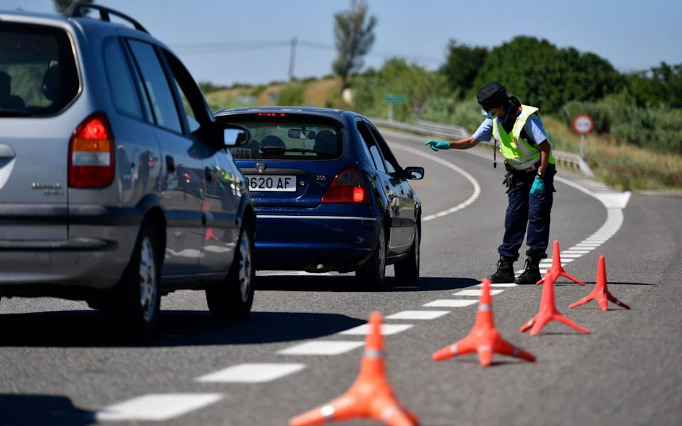 A member of the Catalan regional police force controls a checkpoint after the are around Lerida was isolated from the surrounding region following a surge in new cases - Pau BARRENA / AFP