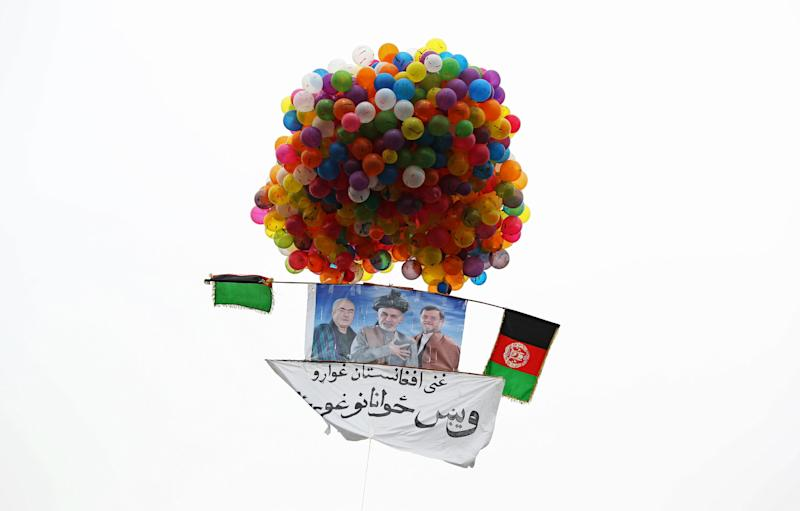 """In this photo taken on Tuesday, April 1, 2014, balloons lift a poster of Afghan presidential candidate Ashraf Ghani Ahmadzai skyward during a campaign rally in Kabul, Afghanistan. Writing on the poster reads, """"We want a reach Afghanistan, we want talented youth."""" (AP Photo/Massoud Hossaini)"""