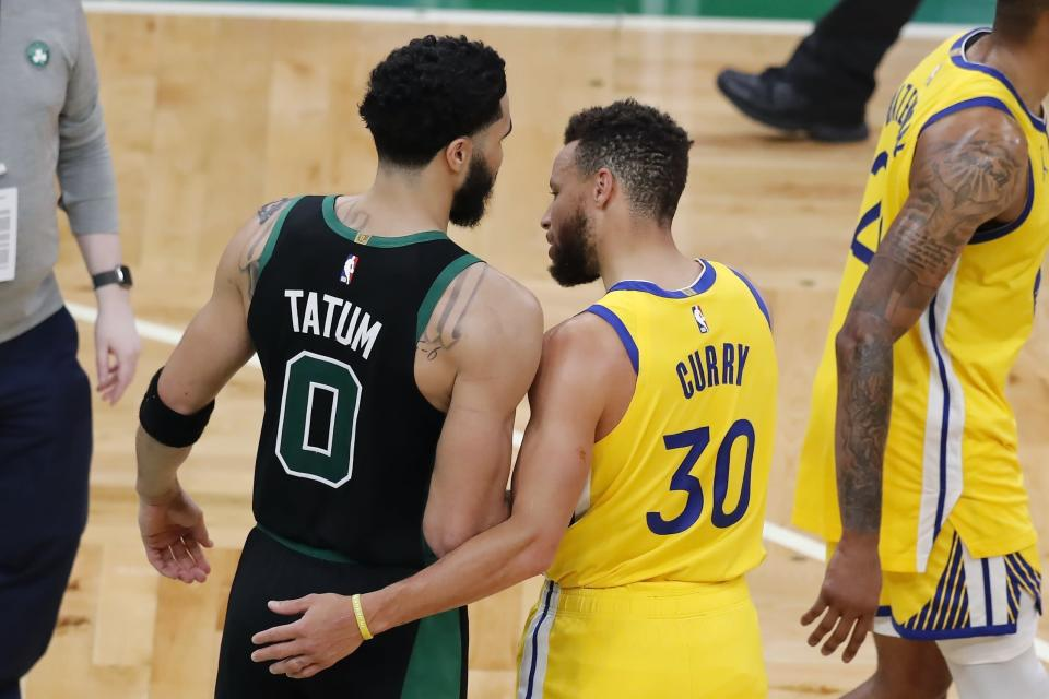Boston Celtics' Jayson Tatum (0) and Golden State Warriors' Stephen Curry (30) talk following an NBA basketball game, Saturday, April 17, 2021, in Boston. (AP Photo/Michael Dwyer)