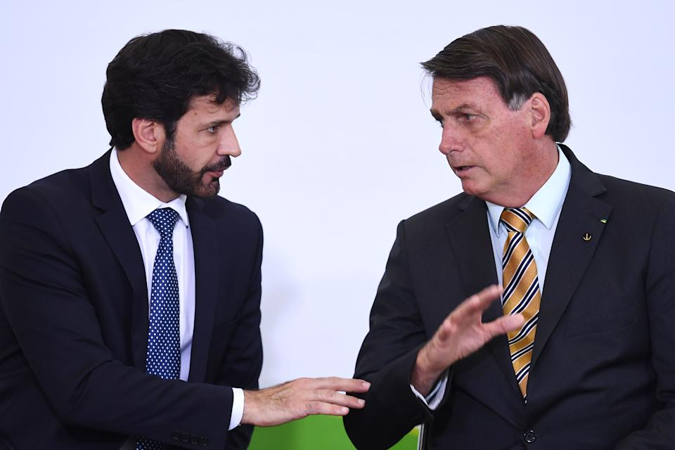 """Brazilian President Jair Bolsonaro (R) speaks with his Tourism Minister Marcelo Alvaro Antonio during the launch of a program for the resumption of tourism, a sector severely affected by the new coronavirus outbreak, at Planalto Palace in Brasilia, on November 10, 2020. - Brazil's decision to halt trials of a Chinese-developed Covid-19 vaccine triggered a politically charged row Tuesday as a top health official expressed """"indignation"""" and far-right President Jair Bolsonaro claimed the ruling as a personal victory. (Photo by EVARISTO SA / AFP) (Photo by EVARISTO SA/AFP via Getty Images)"""