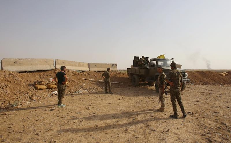 Members of the Kurdish People's Protection Units (YPG) take position in Maarouf in Hasakeh province on July 16, 2015, as they battle Islamic State group jihadists (AFP Photo/Youssef Karwashan)