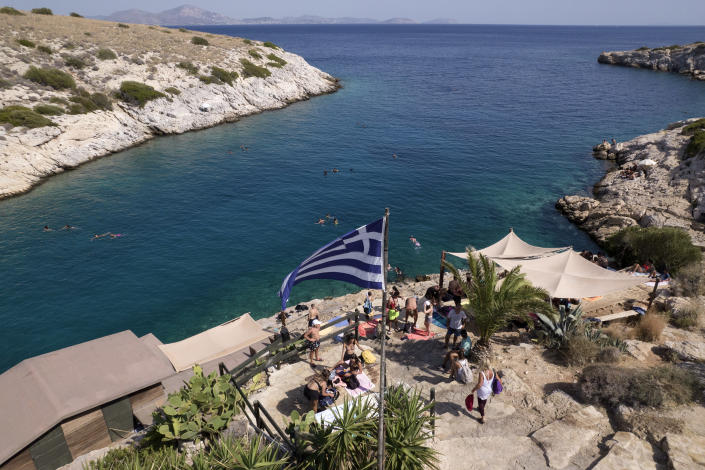 People are pictured next to a beach bar at Vouliagmeni suburb, southwest of Athens, on Thursday, July 29, 2021. One of the most severe heat waves recorded since 1980s scorched southeast Europe on Thursday, sending residents flocking to the coast, public fountains and air-conditioned locations to find some relief, with temperatures rose above 40 C (104 F) in parts of Greece and across much of the region. (AP Photo/Yorgos Karahalis)