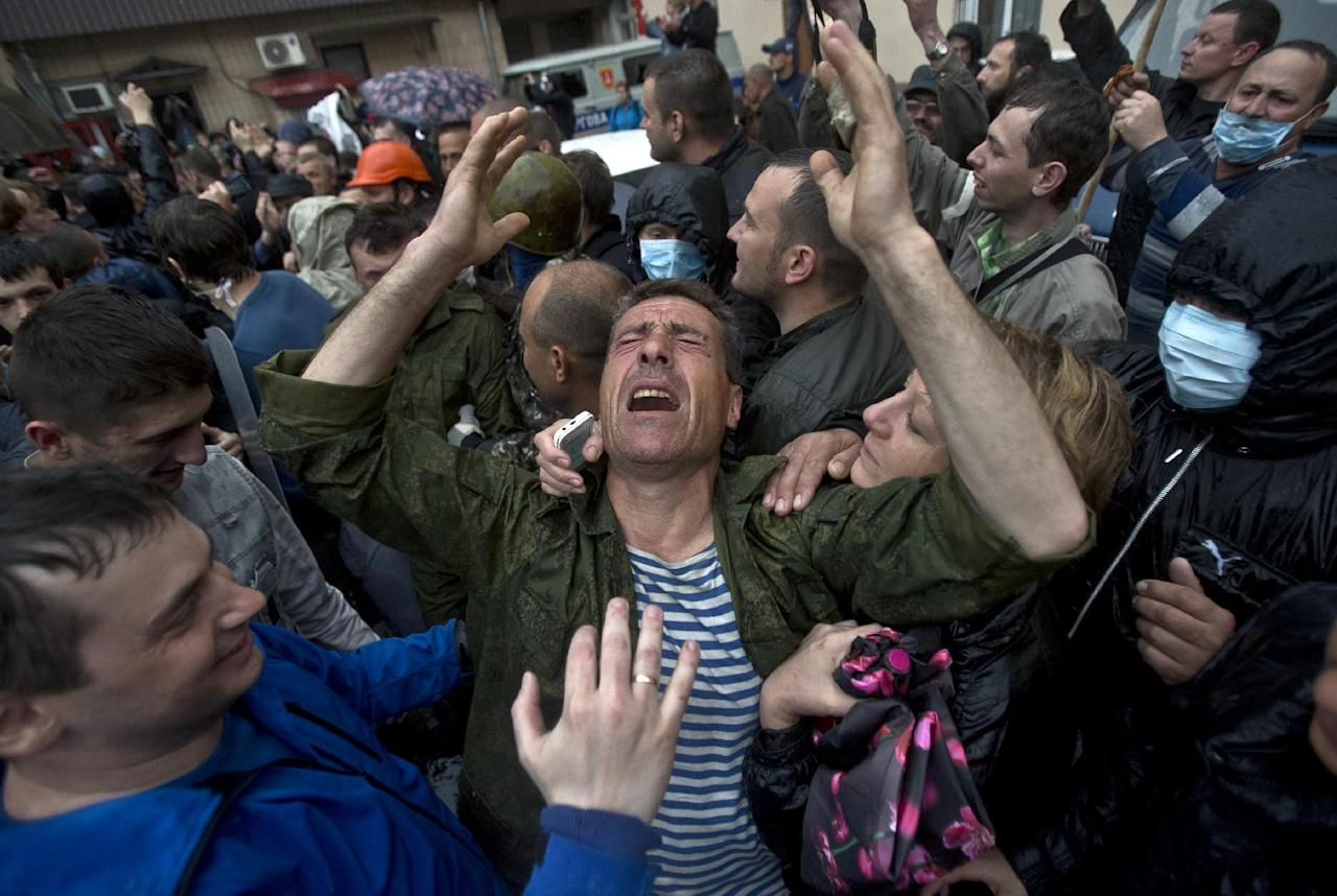 A man cries after being released from a local police station which was stormed by pro-Russian protesters in Odessa, Ukraine, Sunday, May 4, 2014. Several prisoners that were detained during clashes that erupted Friday between pro-Russians and government supporters in the key port on the Black Sea coast were released under the pressure of protesters that broke into a local police station and received a hero's welcome by crowds. (AP Photo/Vadim Ghirda)
