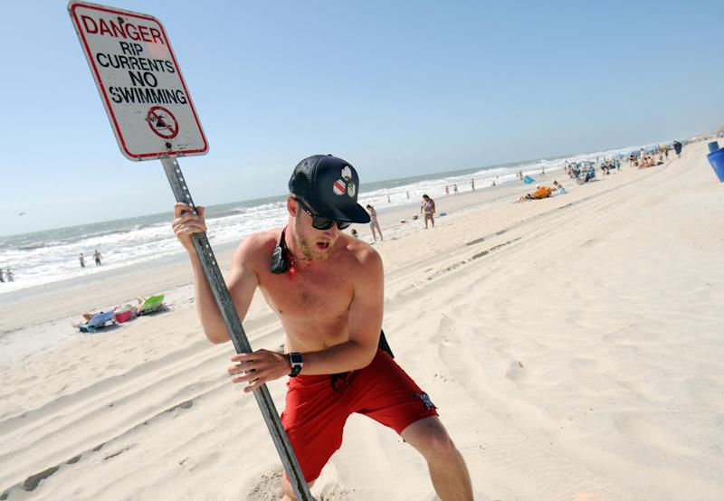 Carolina Beach Ocean Rescue squad leader Evan Anderson places a sign in the sand closing the beach to swimming at Carolina Beach, N.C. Saturday, May 26, 2012. Strong rip currents created dangerous swimming conditions and prompted Carolina Beach Ocean Rescue to close the beach to swimming and not allow people in past their knees.  (AP Photo/The Star-News,Matt Born )