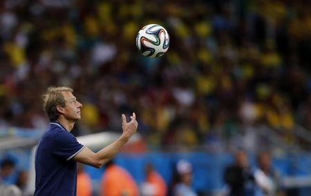 U.S. coach Juergen Klinsmann tosses the ball into the air it rolls over the line for a throw in during their 2014 World Cup round of 16 game against Belgium at the Fonte Nova arena in Salvador