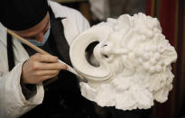 A Venetian artisan mask maker works on an item in a workshop in Venice, Italy, Saturday, Jan. 30, 2021. In another year, masks would be an accepted sign of gaiety in Venice, an accessory worn for games, parties and crowds. Since the onset of the COVID-19 pandemic face masks are worn now to protect, not amuse. (AP Photo/Antonio Calanni)