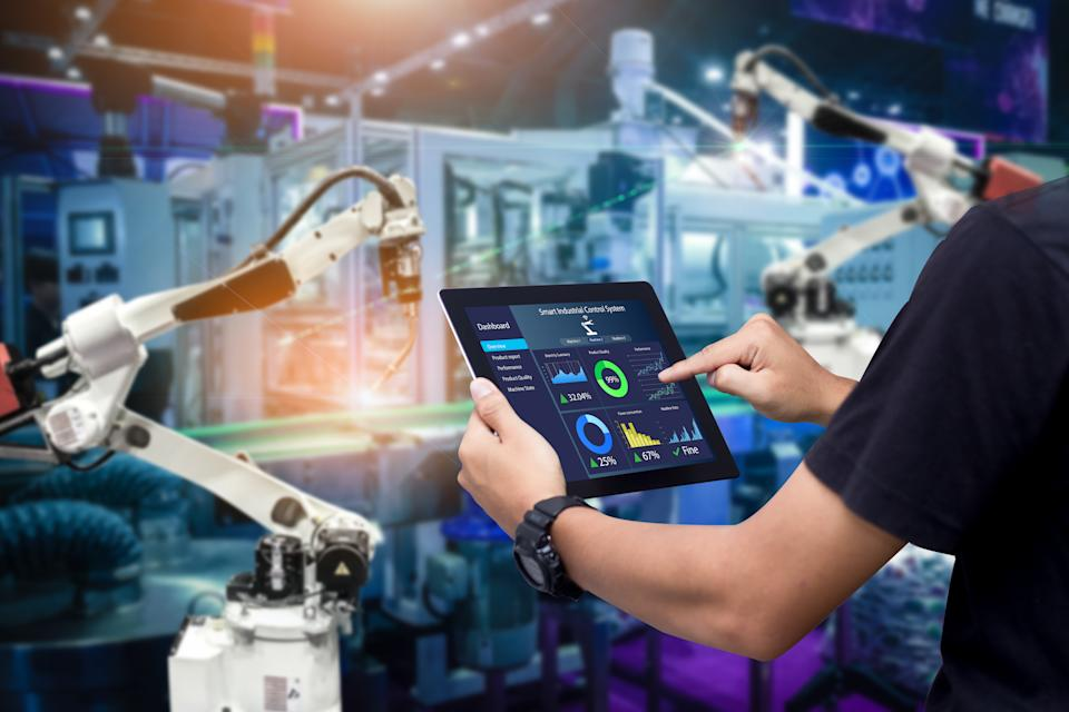 Hands holding tablet on blurred automation machine as background