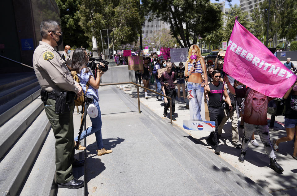 A Los Angeles County Sheriff's deputy watches a procession of Britney Spears supporters march outside a court hearing concerning the pop singer's conservatorship at the Stanley Mosk Courthouse, Wednesday, June 23, 2021, in Los Angeles. (AP Photo/Chris Pizzello)