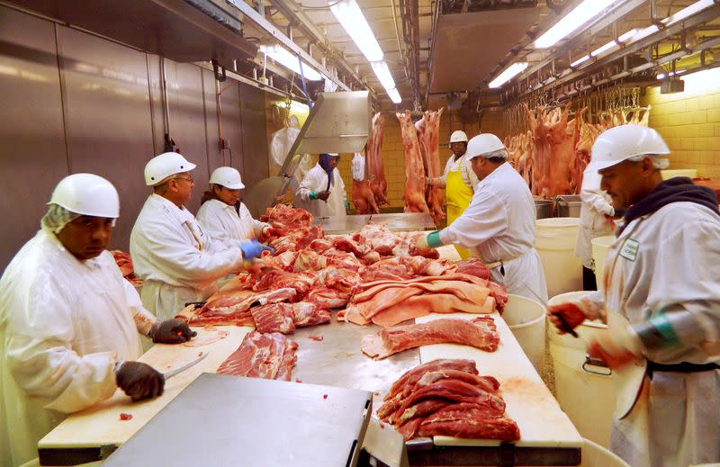 FILE PHOTO: Workers cut pork at Park Packing -- one of the Chicago's few remaining slaughterhouses -- in Chicago
