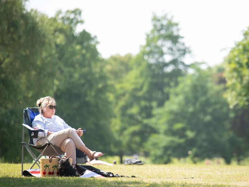 A woman relaxes in the hot weather on Clapham Common: PA
