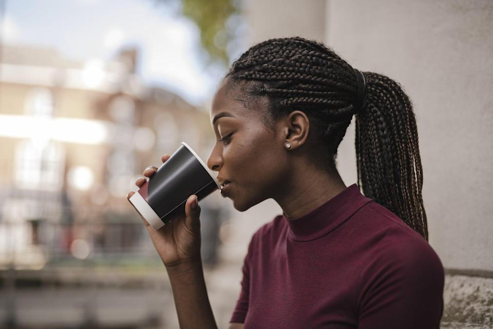 Woman drinking coffee out of a paper cup