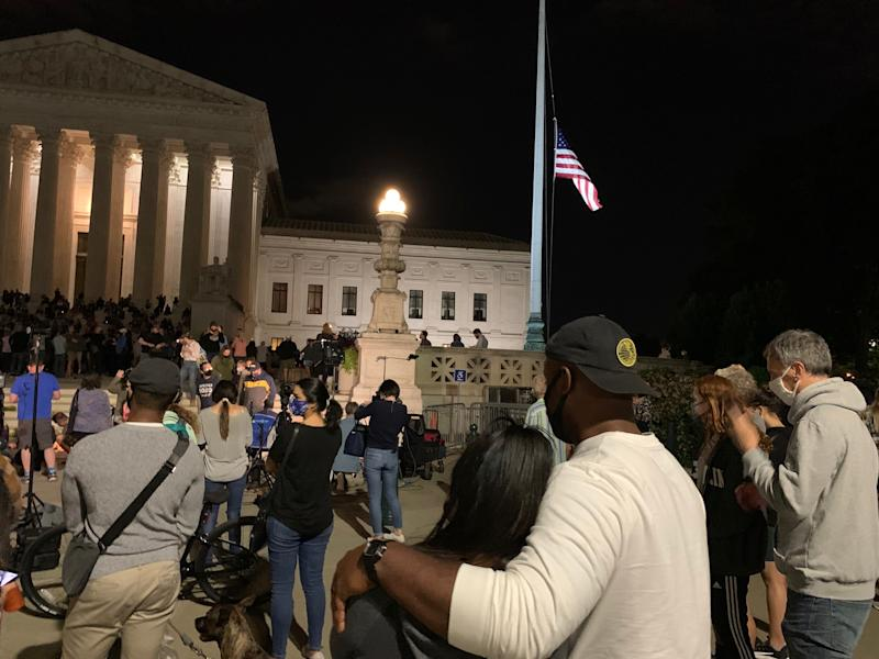 Kent Campbell, 34, and Mekita Rivas, 30. pictured from behind, look on at the somber scene outside the U.S. Supreme Court on Friday night. The couple had just eaten dinner when they heard the news about Ruth Bader Ginsburg's death, and they immediately went to the courthouse to pay their respects.