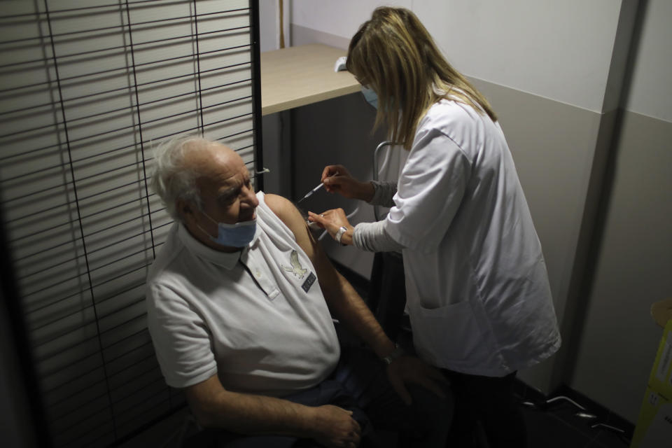 Pierre Cohen, left, receives Pfizer's COVID-19 vaccine at a vaccination site set up in the Marseille soccer Velodrome stadium, during a presentation to the media, in Marseille, Monday, March 15, 2021. The government plans to inoculate 10 million citizens by mid-April, 20 million by mid-May and a total of 30 million, or two-thirds of the adults by summer. (AP Photo/Daniel Cole)