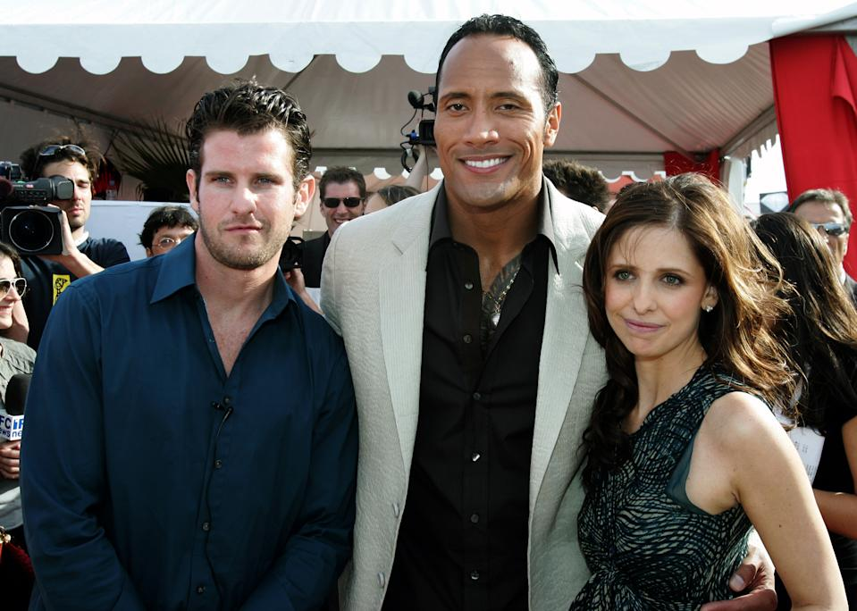 U.S. director Richard Kelly (L) poses with cast members U.S. actor Dwayne 'The Rock' Johnson (C) and U.S actress Sarah Michelle Gellar at a cocktail party for the director's in competition film 'Southland Tales' at the 59th Cannes Film Festival May 21, 2006.      REUTERS/Tom Boland
