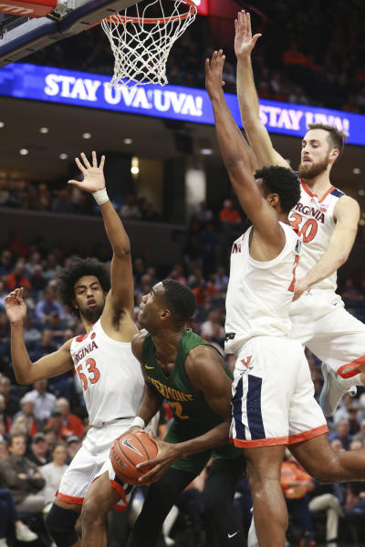 Virginia guard Tomas Woldetensae (53). forward Jay Huff (30) and guard Braxton Key, second from right, defend against Vermont center Daniel Giddens (2) during the first half of an NCAA college basketball game Tuesday, Nov. 19, 2019, in Charlottesville, Va. (AP Photo/Steve Helber)