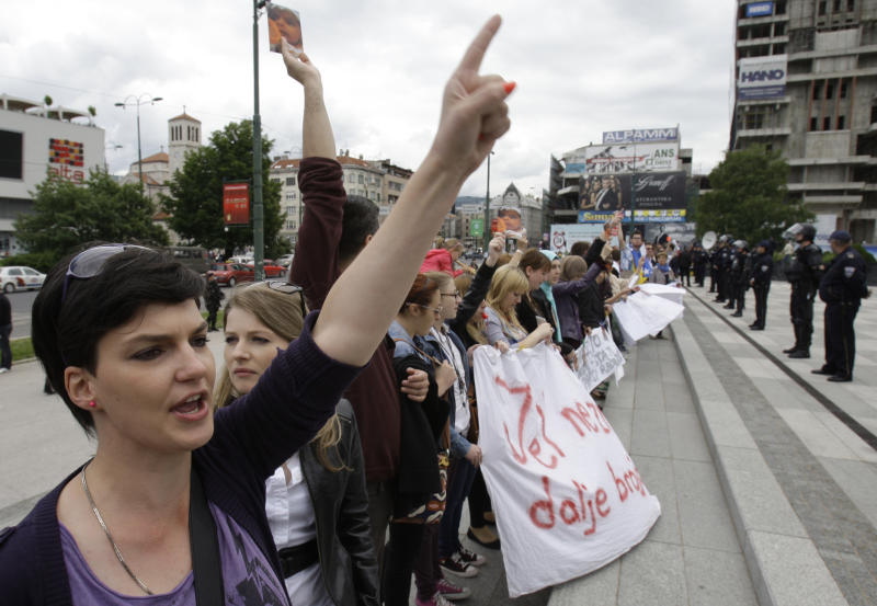 Bosnians protest in front of the Bosnian parliament building in Sarajevo, Thursday, June 6, 2013. Nearly 3,000 people formed a chain around Bosnia's parliament Thursday, saying they won't let politicians go home until they start doing their jobs instead of keeping the country paralyzed with ethnic bickering. What started as a small protest over a new law on personal identification numbers the day before has grown into a blockade of the building, with more people joining the protest every hour. (AP Photo/Amel Emric)