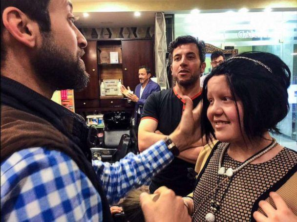 PHOTO: Nehad Dabbas places a handmade natural wig on a child who lost their hair to cancer in Jordan. (Abigail Roberts/ABC News)