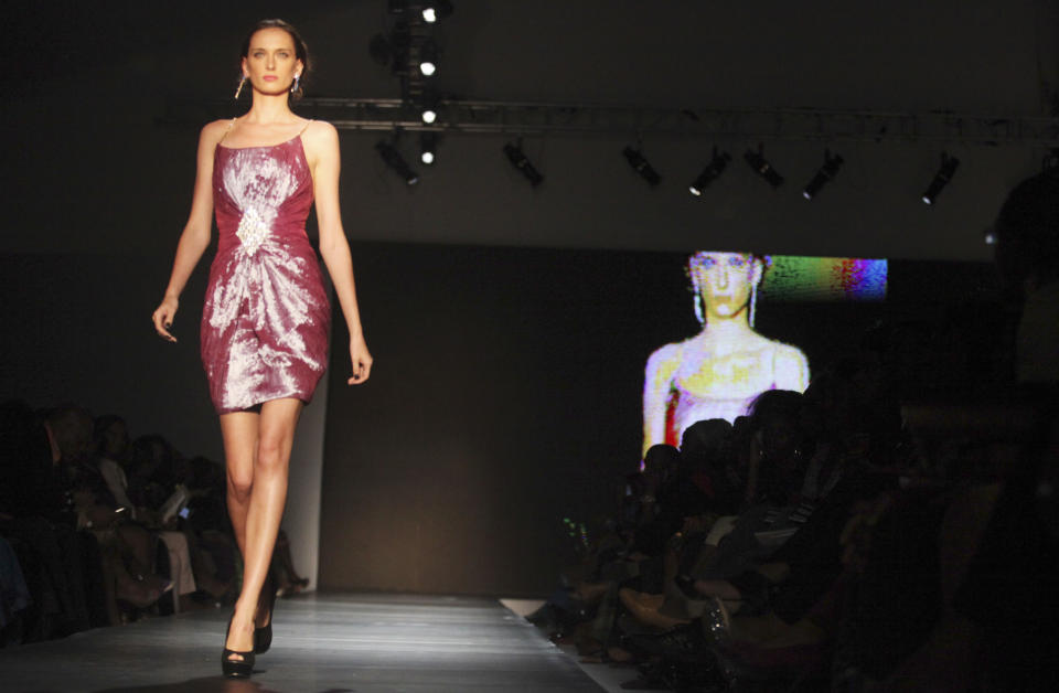 A model displays an outfit at the ARISE Fashion Week event in Lagos, Nigeria on Sunday, March 11, 2012. (AP Photo/Sunday Alamba)