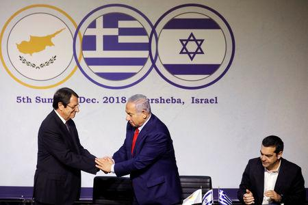 Israeli Prime Minister Benjamin Netanyahu shakes hands with Cypriot President Nicos Anastasiades as Greek Prime Minister Alexis Tsipras sits nearby as the three leaders deliver joint statements at Carasso Science Park in Beersheba, Israel December 20, 2018. REUTERS/Amir Cohen