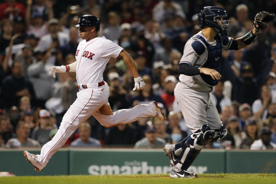 Boston Red Sox's Rafael Devers, left, scores past New York Yankees' Gary Sanchez on a sacrifice fly by J.D. Martinez during the fourth inning of a baseball game, Sunday, Sept. 26, 2021, in Boston. (AP Photo/Michael Dwyer)