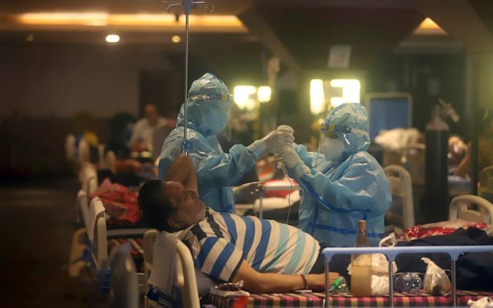 Health workers attend to Covid-19 patients at a makeshift hospital in New Delhi, India, - STR/AP