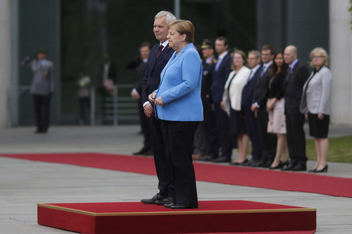 German Chancellor Angela Merkel and Prime Minister of Finland Antti Rinne listen to the national anthems at the chancellery in Berlin, Germany, Wednesday, July 10, 2019. Merkel's body shook visibly as she stood alongside the Finnish prime minister and listen to the national anthems during the welcoming ceremony at the chancellery. (AP Photo/Markus Schreiber)
