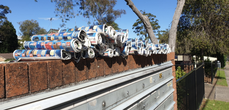 Photo shows piles of catalogues stacked on top of letterboxes in Sydney, NSW.