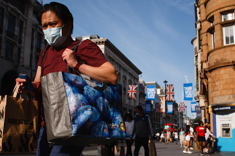 A shopper wearing a face mask carries bags along Oxford Street in London, England, on June 23, 2020. British Prime Minister Boris Johnson announced today that the next stage of lockdown easing in England would proceed on schedule, with pubs, restaurants, hotels, hairdressers, theatres, cinemas, museums, galleries, libraries, theme parks and zoos allowed to reopen from July 4. The two-metre social distancing rule is also to be halved from the same date, with people encouraged to take additional mitigation actions, such as wearing face coverings, when close together. The change, to what is being dubbed 'one-metre plus', is seen as key to the survival of the hospitality sector. (Photo by David Cliff/NurPhoto via Getty Images)