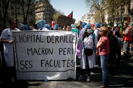 "French health care workers hold a banner reading ""The hospital derails, Macron loses his universities""  during a demonstration against the French government's reform plans in Paris as part of a national day of protest, France, April 19, 2018.  REUTERS/Benoit Tessier"