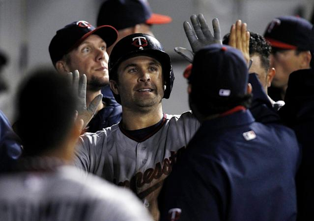 Minnesota Twins' Brian Dozier celebrates after scoring against the Chicago White Sox during the third inning of a baseball game Tuesday, Sept. 17, 2013, in Chicago. (AP Photo/Andrew A. Nelles)