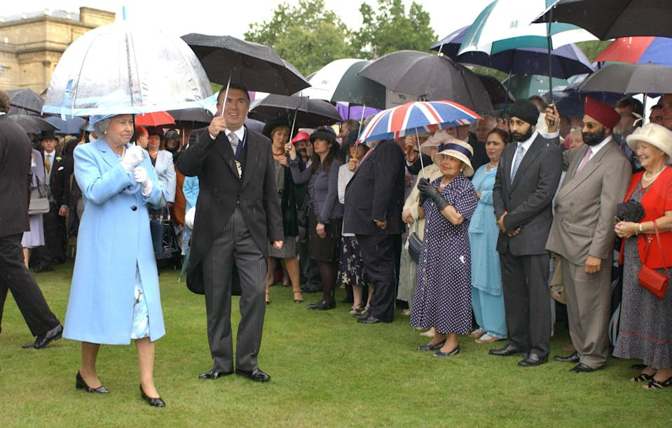 Queen Elizabth II is undaunted by heavy rain during a garden party for the Royal Society of Arts in the gardens of Buckingham Palace, London. Heavy storms have battered Britain over the last two days with thousands of people losing their electricity supplies.   (Photo by Fiona Hanson - PA Images/PA Images via Getty Images)