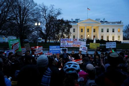 Demonstrators rally against the Trump administration's new travel ban outside of the White House in Washington