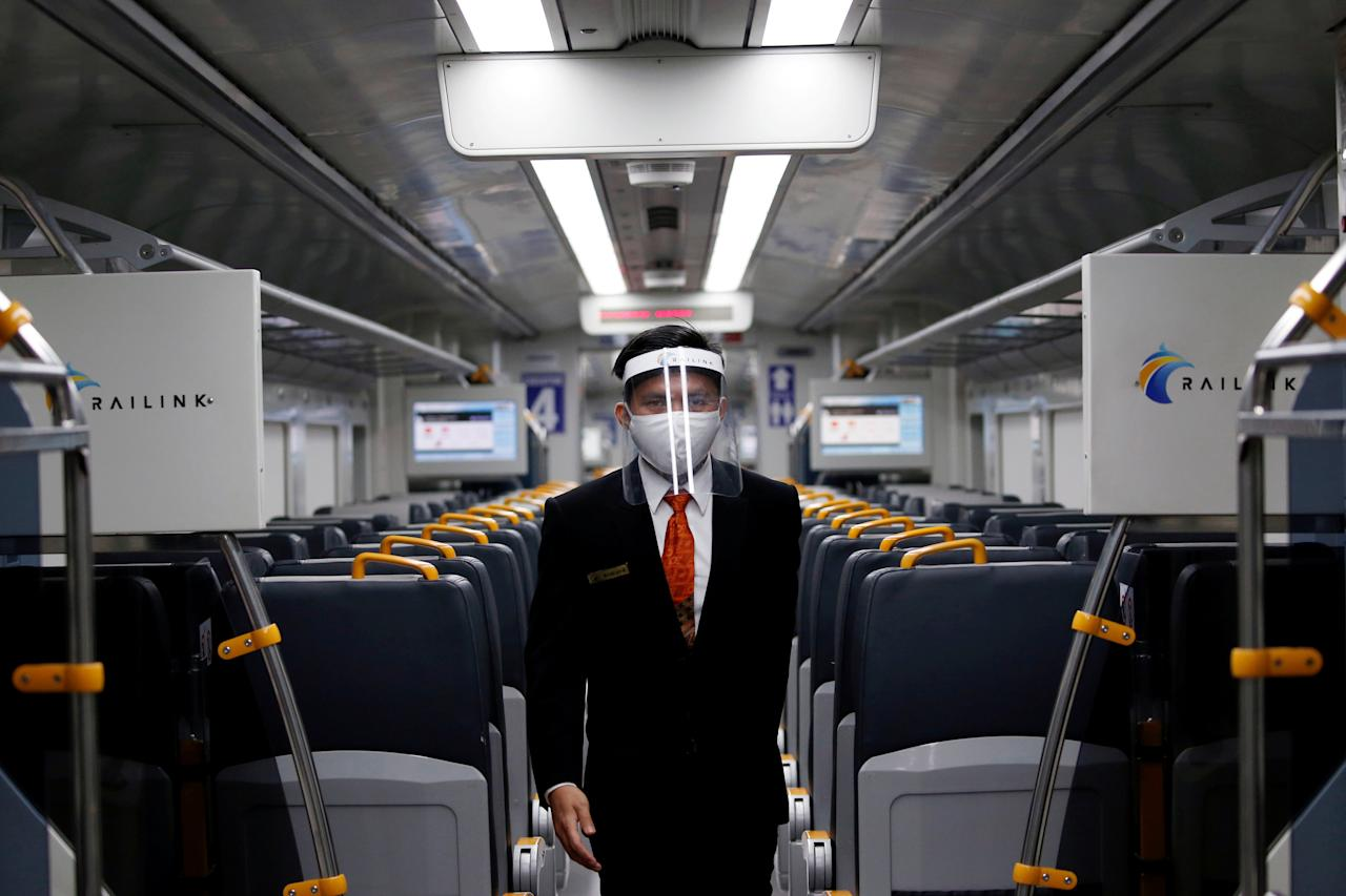 An employee wearing a protective mask and face shield walks inside a Railink train after the government eased restrictions following the coronavirus disease (COVID-19) outbreak in Jakarta, Indonesia, July 2, 2020. REUTERS/Willy Kurniawan     TPX IMAGES OF THE DAY