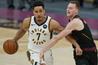 Indiana Pacers' Malcolm Brogdon, left, drives to the basket against Cleveland Cavaliers' Dylan Windler during the second half of an NBA basketball game, Wednesday, March 3, 2021, in Cleveland. (AP Photo/Tony Dejak)